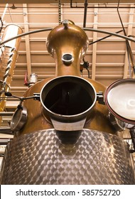 A photo of a whiskey distillery. Featured is a column pot still made from copper and stainless steel. From a worm's eye view, the still soar to the ceiling.