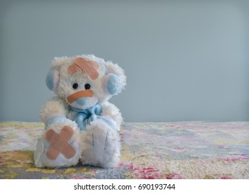 Photo of white bear wearing blue earmuffs and scarf with adhesive bandages on its body.