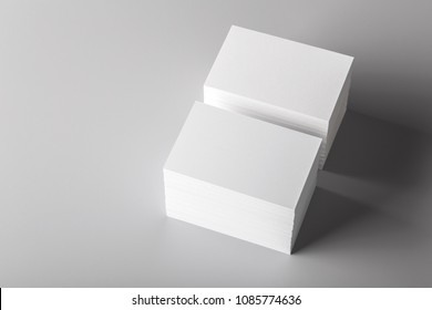 Photo of white business cards isolated on gray background. Template for branding identity. For graphic designers presentations and portfolios. Business Card isolated on gray.