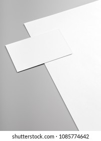 Photo of white business cards and letterhead isolated on gray background. Template for branding identity. For graphic designers presentations and portfolios.