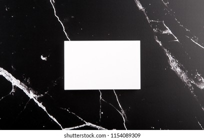 Photo of white business cards on black marble. Template for branding identity isolated on marble background. For graphic designers presentations and portfolios marble premium luxury mock-up.