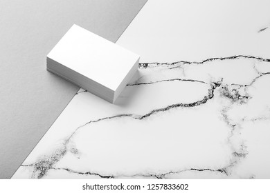 Photo of white business cards on white marble and gray background. Mock up for branding identity isolated on marble background. Business Card mock-up isolated on marble stone