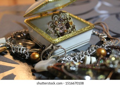 Photo of a white casket with a brown ring and brown jewelry on a black background.