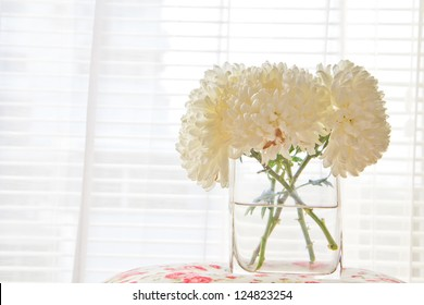 a photo of white chrysanthemum flower in glass vase on table with colorful paint fabric front of window at morning