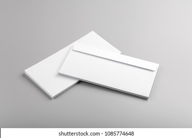 Photo of white envelope isolated on gray background. Template for branding identity. For graphic designers presentations and portfolios. Envelopes isolated on gray. White envelope mock-up.