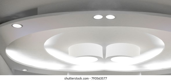 Photo of white hi-tech ceiling with lighting fixtures / spot lamps. Fragment of minimalist modern architecture. Abstract contemporary interior design.