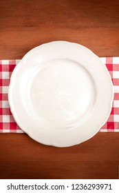 A photo of a white plate on a vichy table cloth on a dark rustic wooden background with a place for text
