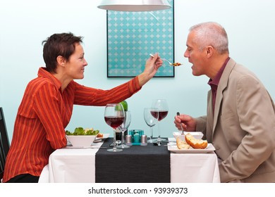 Photo of a wife letting her husband try her food in a restaurant.