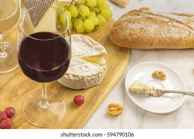 A photo of a wine and cheese tasting, with bread, grapes, and a glass of red wine