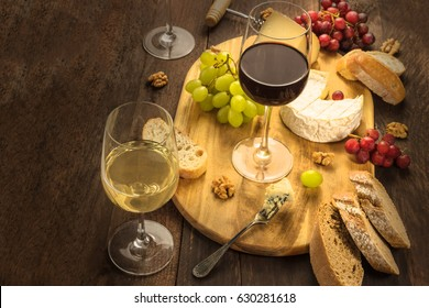 A photo of a wine and cheese tasting, with bread, grapes, and wine accessories, as well as a place for text