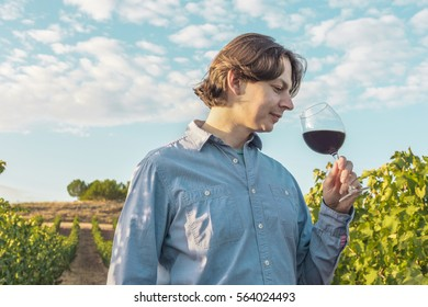 A photo of a winemaker tasting his wine in a vineyard