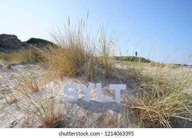 Photo witk Sylt Letters in the sand  from the dunes and the coast  of sylt island germany a take in the  late sun light