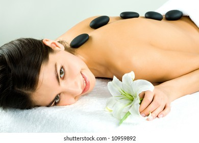 Photo of woman with black stones on her bare back and holding the flower