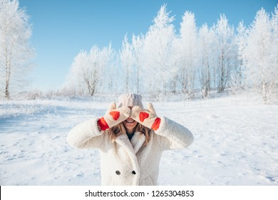 Photo of woman in fur coat and gloves with red hearts closing her eyes over white snow in magic winter day