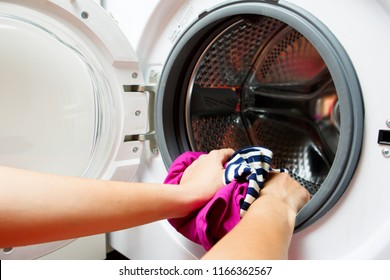 Photo of woman hands folding colorful things in washing machine with open door