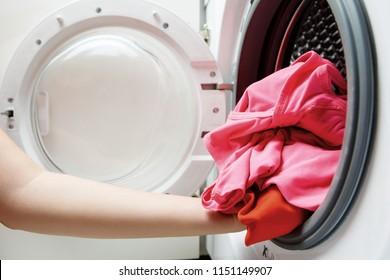 Photo of woman hands folding things in washing machine