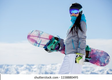 Photo of woman hiking helmet with snowboard on snow mountains background