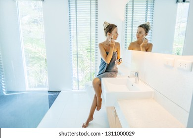 Photo of woman looking at mirror and applying makeup in luxury bathroom. Making everyday morning treatment.