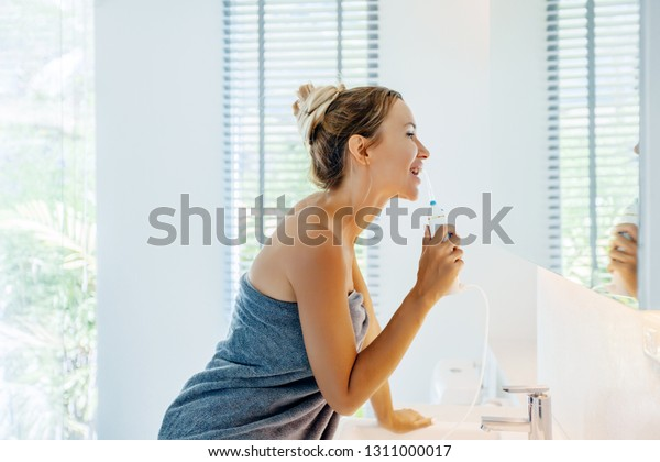 Photo of woman looking at mirror and brushing teeth with water floss. Doing everyday morning routine in bathroom. Portable irrigation system at home.
