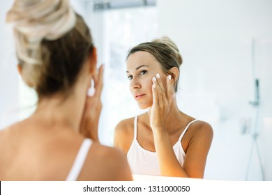 Photo of woman looking at mirror and touching her skin. Making everyday morning treatment in bathroom.