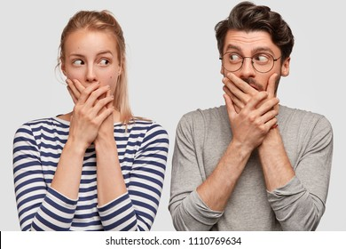 Photo of woman and man lovers keep mouthes closed, look in puzzlement at each other, promise not tell about their ties to husband or wife, isolated on white background. Omg, what have we done?