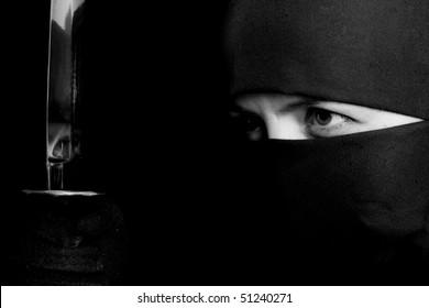 Photo of woman in ninja suit with wakizashi on black background. BW photo