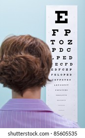 Photo of a woman at the opticians having her eyesight tested using a eye chart to see if she needs glasses.