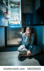 Photo of woman in pajamas eating on floor next to fridge at night