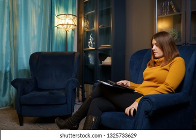 Photo of woman psychologist with tablet in hand sitting at blue chair.