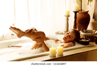 Photo of a woman relaxed at luxury spa salon, picture of young beautiful lady taking bath at home, image of pretty female bathing with soap foam and candles in hotel room, cute girl relax in jacuzzi
