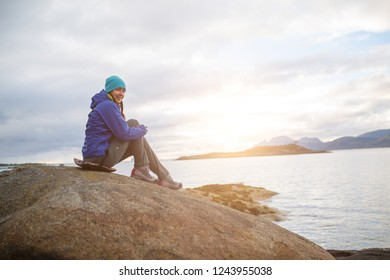 Photo of woman sitting on stone in seashore