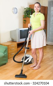 Photo of woman in skirt vacuuming  living room