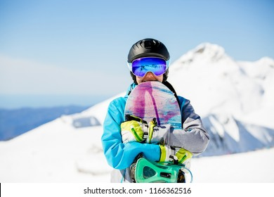 Photo of woman tourist in helmet looking into camera with snowboard in hands
