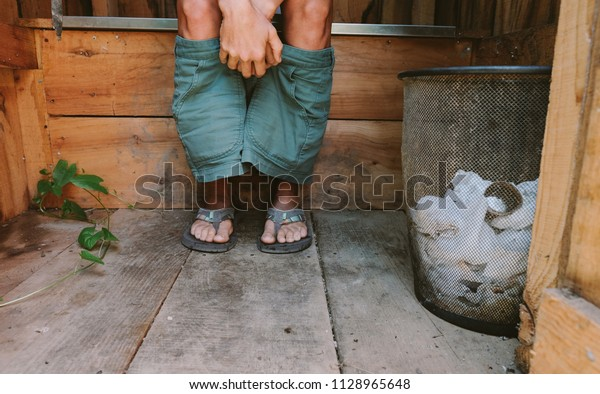 A photo of Woman using an Outdoor Composting Toilet
