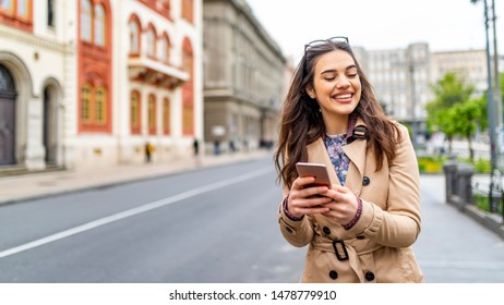 Photo of a woman using smart phone. Beautiful woman texting on the street. Beautiful woman spending time in the city. Fashionable woman with smart phone