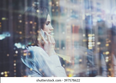 Photo woman wearing white shirt, talking smartphone and holding business plans in hands. Open space loft office. Panoramic windows, night city background. Horizontal mockup, bokeh. Film effect