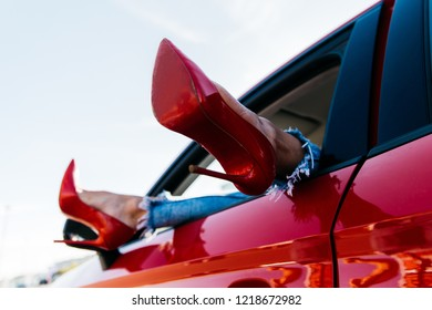 c210aef0207 Photo of woman s legs in red shoes and jeans protruding from red car