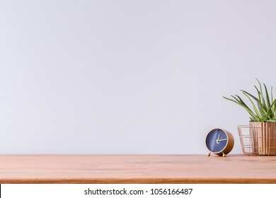Photo of wooden home office desk with black and gold clock and fresh green plant against white empty wall