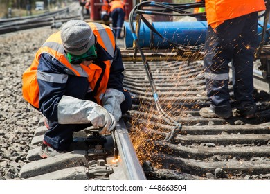 photo of worker doing gas cutting on rails