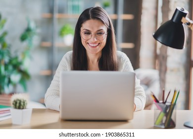 Photo of worker lady sit desk work computer look screen beaming smile wear eyeglasses white pullover in living room home indoors