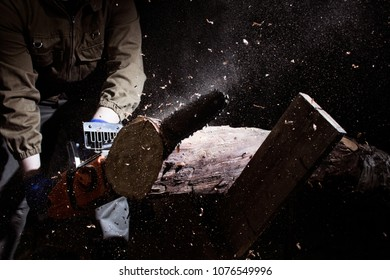 Photo of a worker in outfit with blue gloves cutting wood log on black background.