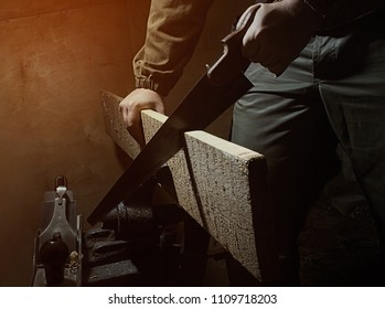 Photo of a worker in outfit with blue gloves using handsaw with wooden board on black background with upper light.