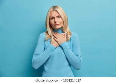 Photo of wrinkled serious woman presses hands to chest makes gratitude gesture looks with sad expression at camera dressed casually isolated on blue background. Thankful touched middle aged lady