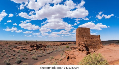 Photo of Wukoki Pueblo in Wupatki National Monument: an Ancestral Puebloan ruin located near Flagstaff Arizona. Clear blue skies and white cloud accent the red stone ruins.