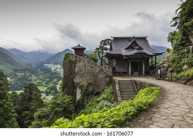 A photo of Yamadera buddhist temple, Japan. A traditional wooden building in the foreground, in the background beautiful rural landscape