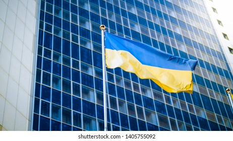 Photo of yellow and blue Ukrainian flag against modern business office building