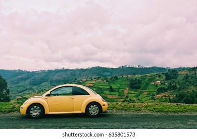 Photo of a yellow Volkswagen Beetle on a road trip through a hilly region on a cloudy day