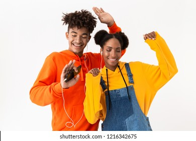 Photo of young african american couple in colorful clothes dancing while listening to music together with earphones isolated over white background