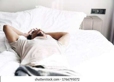 Photo of young african american man with beard lying on bed after sleep at bright room