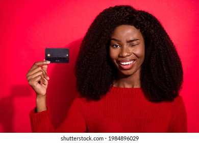 Photo of young afro girl blink eye happy positive smile hold bank credit card payment advice isolated over red color background